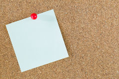 Red pin on post-it note. With cork board background Stock Photography