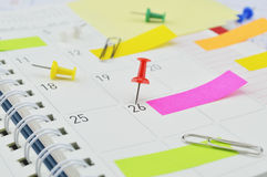 Red pin with post It notes and pin on business diary page Royalty Free Stock Images
