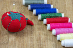 Red pincushion with pins and line of colourful threads Royalty Free Stock Photography