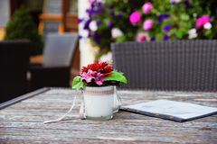 Red and Pink Artificial Flower Table Decor on Brown Wooden Table Shallow Focus Photography stock photos