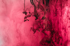 Red, pink, black, white ink in water. Sunshine lighting. Dynamic. Movement of paint in the water. Side view stock photography