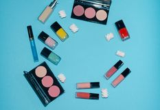 Red, pink and blue lipsticks. Rouge palettes. Сoncealer, red, pink and yellow nail polish. Beauty products on blue background. Near pink and white marshmallows Stock Image