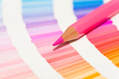 Red and pink colored pencils and color chart of all colors Stock Photo