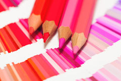 Red and pink colored pencils and color chart of all colors. Red and pink colored pencils and color chart Royalty Free Stock Photos