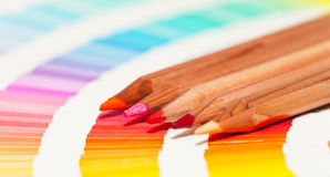 Red and pink colored pencils and color chart Stock Photos
