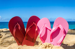 Red and pink flip flops on the sandy beach Stock Photography