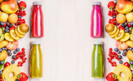 Red,pink,green and yellow smoothies and juices beverages in bottles with various fresh organic fruits and berries ingredients on w. Hite wooden background, top Royalty Free Stock Photography