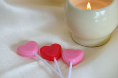 Red and Pink heart shaped lollipops with candle Royalty Free Stock Images