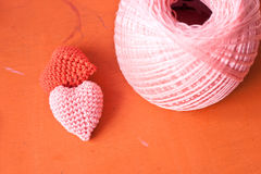 Red and pink knit heart. The heart knit with red and pink yarn on orange table Stock Image