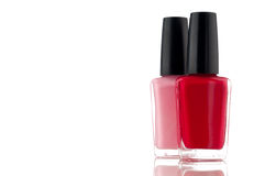 Red and pink nail polish on a white surface Royalty Free Stock Photos