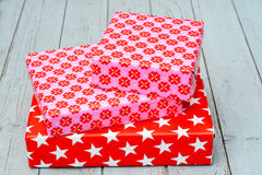 Red and pink star flower pattern christmas gifts with on a wooden shelves background Royalty Free Stock Photos