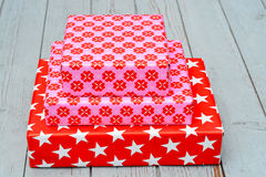 Red and pink star flower pattern christmas gifts on a wooden shelves background Stock Photos