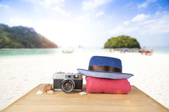 Red pink tower, blue hat, old vintage camera and shells over woo Royalty Free Stock Image