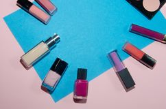 Red, pink and violet lipsticks. Rouge palettes, concealer and nail polish. Decorative cosmetics on blue and pink background. Top v. Iew, flatlay. Copyplace Royalty Free Stock Photo