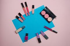 Red, pink and violet lipsticks. Rouge palettes, concealer and nail polish. Decorative cosmetics on blue and pink background. Top v. Iew, flatlay. Copyplace Stock Photos