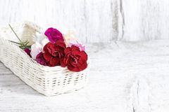 Red, pink and white carnation flowers. In wicker basket on wooden background. Copy space Stock Photo