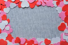 Red, pink, and white heart shaped cut-outs frame on grey fabric background royalty free stock images