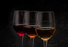 Red, pink, white wine on black background Stock Photos