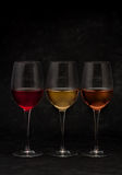 Red, pink and white wine in glasses. On black grunge background royalty free stock images