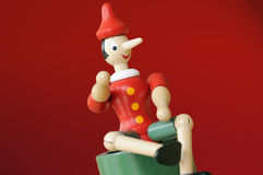 Red Pinocchio. Pinocchio wooden puppet isolated on a red background royalty free stock photo