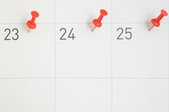 Red pins pinned on the dates of the month on calendar paper stock photos