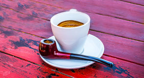 Red pipe and espresso coffee on red table Stock Images