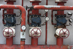 Red pipes with valves and manometers Royalty Free Stock Image
