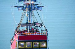 Red pirate ship with Jolly Roger flag closeup. Closeup of a red pirate ship cruising out on the water with a Jolly Roger flag flying royalty free stock photo