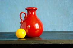 Red pitcher and yellow billiards ball Stock Images