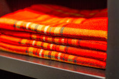 Red plaid checkered lying on a dusty closet shelf Royalty Free Stock Photo