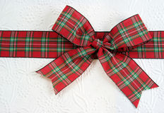 Red Plaid Christmas Bow. A plaid christmas bow on decorative white paper Royalty Free Stock Photo