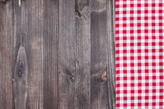 Red plaid cloth on dark wood Royalty Free Stock Image