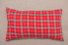 Red plaid pillow on sofa Stock Image
