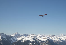 Red plane flying over the alps Stock Photos
