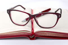 Red Daily planner with eyeglasses and pen Stock Images