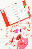 Red planning with plastic butterfly and pink stationary over whi. Te wooden background, vertical shot Stock Image