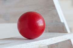 Red plastic ball on white shelf, light background Royalty Free Stock Photo