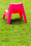 Red plastic chair on  grass Royalty Free Stock Image