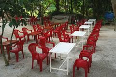 Colorful red and white plastic chairs and tables at an outdoor cafe in rural Vietnam. Red plastic chairs and white plastic tables lined up in tidy rows ready for stock photo