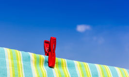 The red plastic clothespin is on the clothesline with blue sky b. The red plastic clothespin is on the clothesline and colored cotton with blue sky background Stock Photography