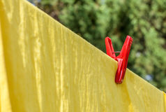 The red plastic clothespin is on the clothesline with yellow cot. The red plastic clothespin is contrasting on the clothesline with yellow cotton cloth Stock Photo