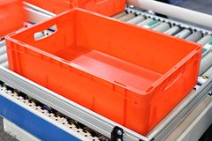Red plastic containers on roller conveyors in an automated high bay warehouse. The boxes are used in the logistics chain transport. Ing the produced goods stock photography