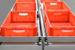 Red plastic containers on roller conveyors in an automated high bay warehouse. The boxes are used in the logistics chain transport. Ing the produced goods stock photos