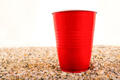 Red plastic cup on beach sand Stock Images