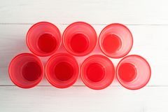 Red plastic cups on a white wooden table, top view.  stock images