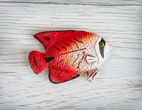 Red plastic fish toy, symbolic object. Humorous red plastic fish toy on the wooden background. Symbolic object. Sea life Stock Photography