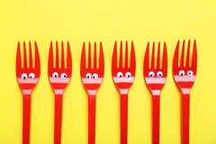 Red plastic forks. With googly eyes on a yellow background Royalty Free Stock Photos