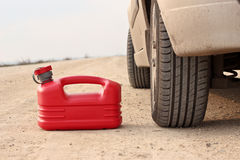 Red plastic fuel canister on dirt road with car Royalty Free Stock Photography