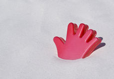 Red plastic hand toy on a white sand beach. A red plastic toy on a white sand beach in the shape of a hand Royalty Free Stock Photo