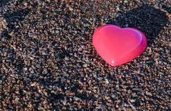 Red plastic heart lies on the sand. pea gravel.  stock photos